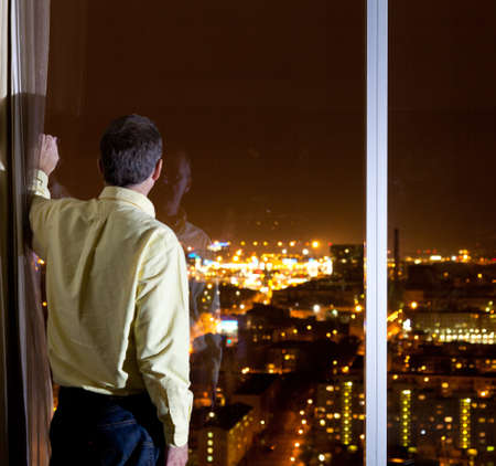 Midden leef tijd man kijkt uit over een stad uit een hoog raam in een hotel of kantoor Stockfoto