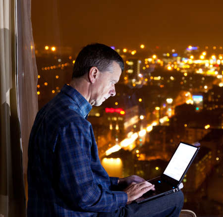 Middle aged man typing on laptop and looking out over a city from a high window in a hotel or office photo