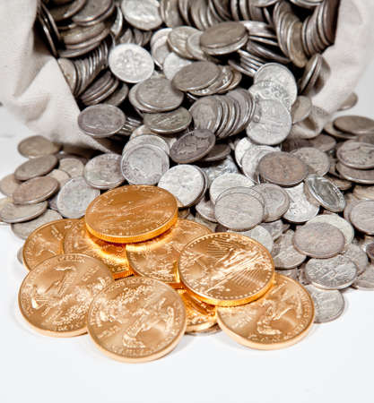 sterlina: Linen bag of old pure silver coins used to invest in silver as a commodity with a selection of Golden Eagle gold coins