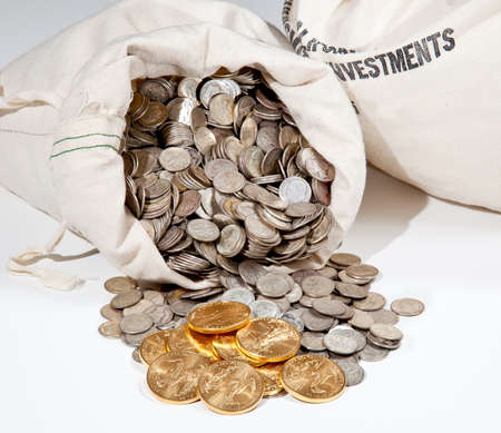 Linen bag of old pure silver coins used to invest in silver as a commodity with a selection of Golden Eagle gold coins Stock Photo - 8287475