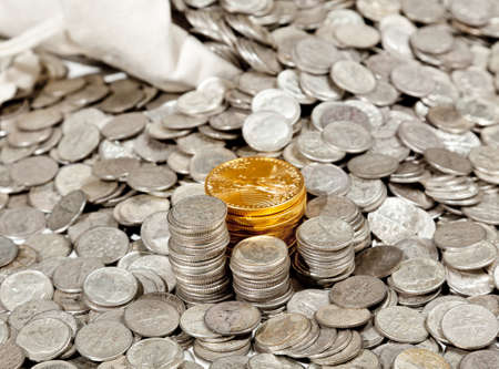Linen bag of old pure silver coins used to invest in silver as a commodity with a selection of Golden Eagle gold coins Stock Photo - 8287484