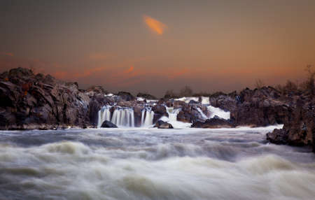 Waterfalls on the Potomac river near Washington DC after sunset as the setting sun illuminates the clouds over Great Falls