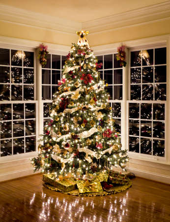 Christmas tree with presents and lights reflecting in windows around the tree in modern home photo
