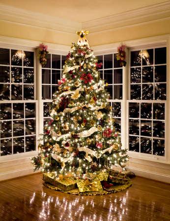 Rbol de Navidad con regalos y luces que refleja en ventanas alrededor del árbol en el hogar moderno Foto de archivo - 8470312
