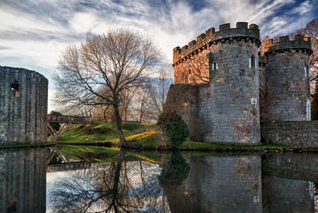 Ancient Whittington Castle in Shropshire, England reflecting in a calm moat round the stone buildings and processed in HDR