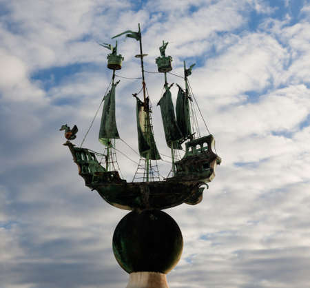 Small copper sailing ship set against a cloudy blue sky and showing its green colored copper sheen Standard-Bild