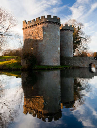 reflecting: Ancient Whittington Castle in Shropshire, England reflecting in a calm moat round the stone buildings