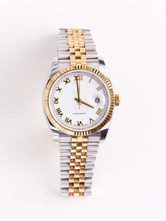 Expensive gold bevelled watch with white face and gold hands and numerals against white background photo