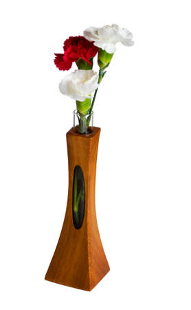 Single red and two white spray carnation blossoms in a carved teak vase with unique opening showing the stem photo