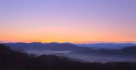 daybreak: Sun rising over snowy mountains of Smokies in early spring with fog in valleys