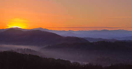 ridge: Sun rising over snowy mountains of Smokies in early spring with fog in valleys