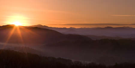 Sun rising over snowy mountains of Smokies in early spring with fog in valleys