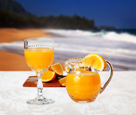 Orange juice in cut glass goblet with small jug and slices of orange in front of sandy beach and set on white linen tablecloth Stock Photo
