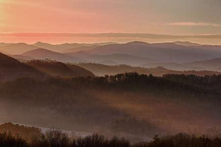谷で霧と早春のスモーキーズの雪の山の上に昇る太陽 写真素材 - 9046711