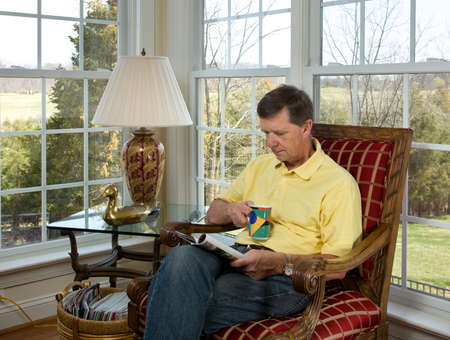 reading lamps: Senior male sitting in corner overlooking garden in modern room and reading a magazine