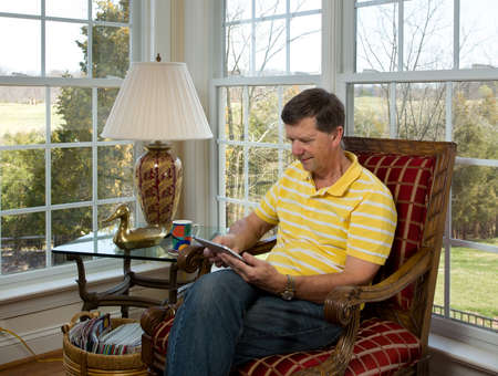 Senior male sitting in corner overlooking garden in modern room and watching from a tablet computer photo