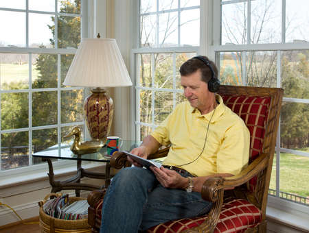Senior male sitting in corner overlooking garden in modern room and watching from a tablet computer Stock Photo - 9182024