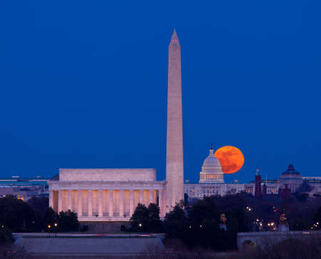 Large full moon rises through the haze over the Capitol building in Washington DC with Lincoln Memorial and Washington Monument aligned photo