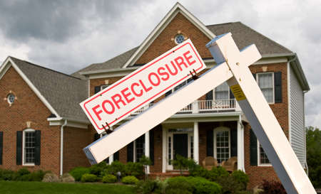 Leaning foreclosure sign in front of a modern single family home on a cloudy cold day photo