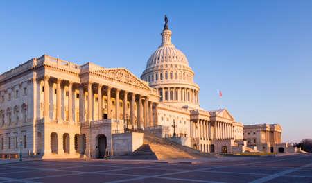 Edificio del Capitolio en Washington DC iluminado temprano en la mañana por el sol y dando un tono rojo y naranja a la tradicional escena
