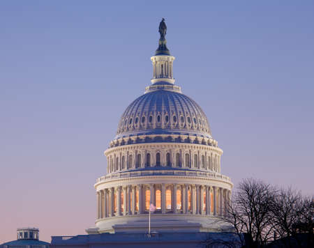 Brightly lit dawn sky behind the illuminated dome of the Capitol in Washington DC with the Statue of Freedom in the sunlight photo