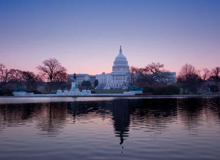 Brightly lit dawn sky behind the illuminated dome of the Capitol in Washington DC with the pool and statues photo