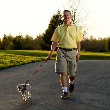 ancianos caminando: Puesta de sol resalta los bordes de un peque�o perro como hombre retirado activo regresa de un paseo