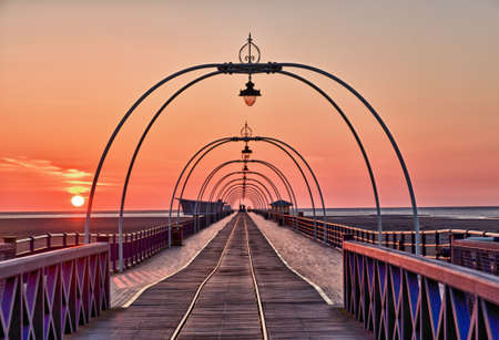 View down center of Southport Pier at sunset with the ornate lights framing the distant horizon