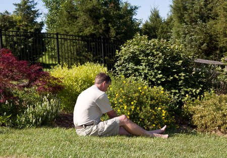 baby boomer: Baby boomer sitting on the grass lawn and digging for weeds in a flowerbed