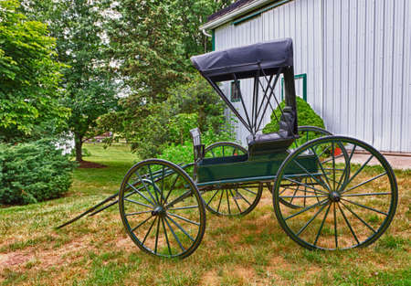HDR image of a green horse drawn buggy by a white barn on a grassy slope photo