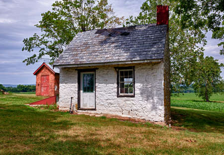 white washed: Old stone white washed cottage on farmland with trees and plants in the background. Slate roof