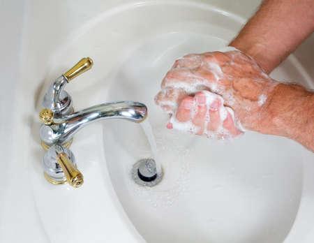 lavandose las manos: Senior hombre lavado de manos en receptor moderno con jab�n y jabonosa espuma Foto de archivo