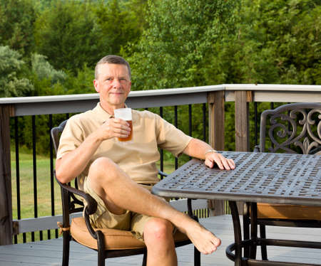 Middle aged man sitting on cast aluminium garden table on deck and drinking a glass of beer in back yard photo