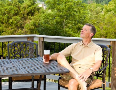 disfrutar: Hombre de mediana edad sentado en mesa de fundici�n de aluminio en la cubierta y beber un vaso de cerveza en el patio trasero