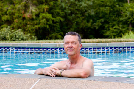 Senior male relaxing by the side of a modern swimming pool in back yard garden and facing the camera with smile photo