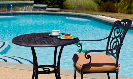 Coffee and plate on cast aluminum table and single chair by the side of swimming pool in back yard