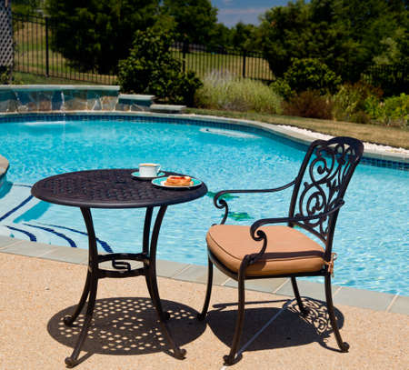 lawn chair: Coffee and plate on cast aluminum table and single chair by the side of swimming pool in back yard