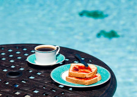 side table: Coffee and plate on cast aluminum table and single chair by the side of swimming pool in back yard