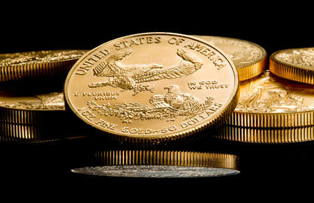 Close up of a solid gold eagle one ounce coin stacked on other coins and reflected in black surface photo