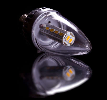 Latest LED light bulb in candle shape and reflecting off a black surface Stock Photo