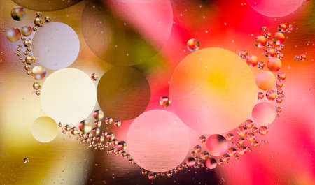 Abstract oil droplets in water reflecting the colors of a background to give a planet effect Stock Photo - 10085775