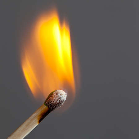 wood burning: Green coated match head starts to burn with light blue smoke