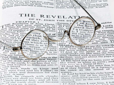 book of revelation: Old fashioned round reading glasses laying on a page from the bible on the revelation Stock Photo