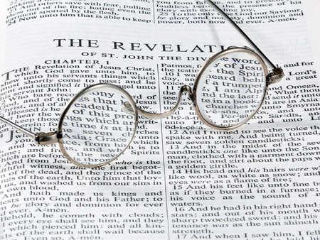 Staromódní kulaté brýle na čtení, kterým na stránku z bible na zjevení