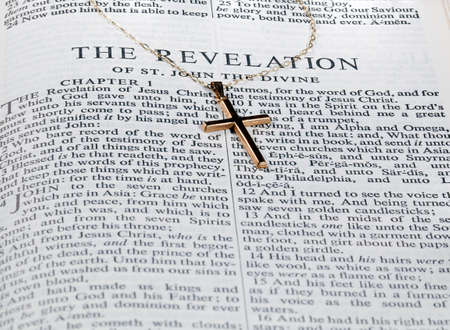 book of revelation: Old fashioned gold cross and chain laying on a page from the bible on the revelation