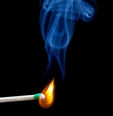 match head: Green coated match head starts to burn with light blue smoke