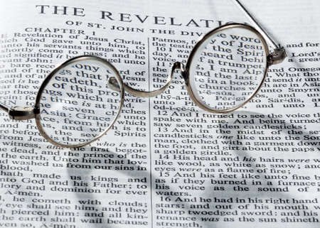 Old fashioned round reading glasses laying on a page from the bible on the revelation with strong shadow