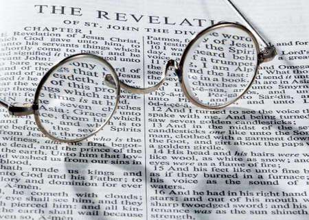 leyendo la biblia: Viejo anticuado ronda leyendo gafas tendido en una p�gina de la Biblia sobre la revelaci�n con fuerte sombra Foto de archivo