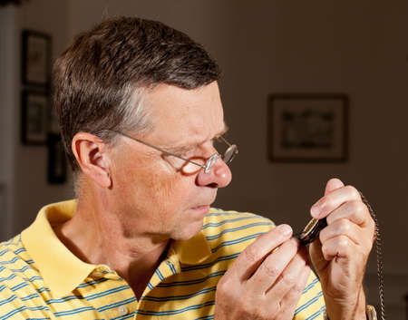 Senior repairing an old pocket watch with screwdriver and wearing very strong lens glasses to magnify the mechanism photo