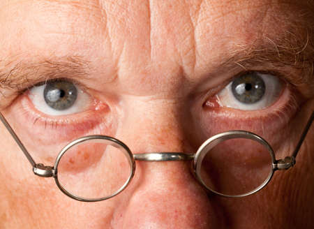 Portrait of a senior male with the focus on magnifying glasses and the eyes are in focus photo